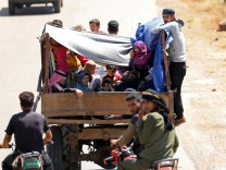 Internally displaced people from Deraa province ride on a back of a truck near the Israeli-occupied Golan Heights in Quneitra