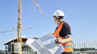Construction worker with blueprint on construction site model released Symbolfoto property released
