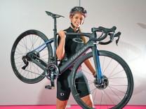 Eine Frau mit Fahrradhelm hebt das E-Bike-Rennrad Wilier Cento 1 Hybrid SL in die Höhe.