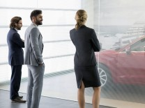 Car sales people and customer looking at car Car sales people and customer looking at new car in car