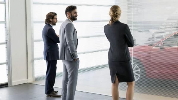 Car sales people and customer looking at car Car sales people and customer looking at new car in car