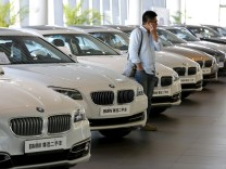 A man takes a look at second-hand BMW cars at a dealer shop in Beijing