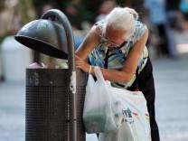 Eine alte Dame durchsucht einen Mülleimer in Weimar