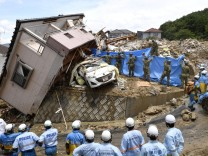 Rescue workers look for missing people in a house damaged by heavy rain in Kumano town