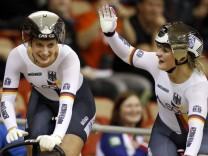 Germany's Welte and Vogel celebrate their gold medals during women's team sprint final at the 2013 UCI Track Cycling World Championships in Minsk