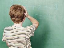 Kind steht im Unterricht vor Tafel