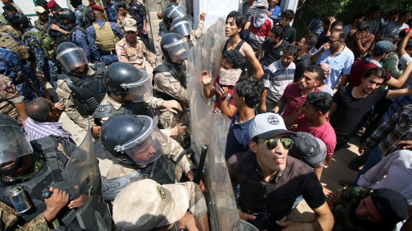 Iraq: Protesters scuffle with security forces near the main provincial government building in Basra