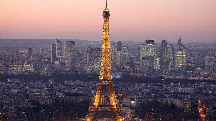 A general view show the illuminated Eiffel Tower and the skyline of La Defense business district at night in Paris