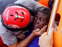 A crew member of NGO Proactiva Open Arms rescue boat embraces African migrant in central Mediterranean Sea