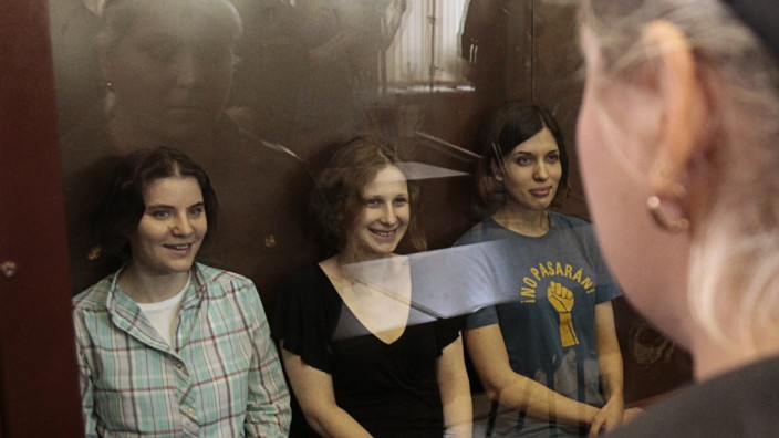 Members of the female punk band 'Pussy Riot' sit in a glass-walled cage during a court hearing in Moscow