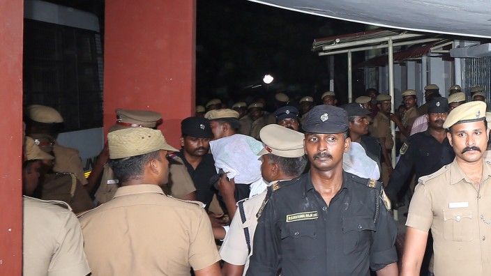 Police escort one of the men (face covered) accused of raping a 12-year girl inside the high court premises in Chenna