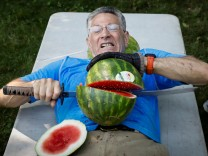 Ashrita Furman, who holds more Guinness World Records than anyone, attempts to set a new record for slicing the most watermelons in half on his own stomach in one minute in New York