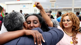 Relatives embrace after meeting at Asmara International Airport, after one of them arrived aboard the Ethiopian Airlines flight in Asmara