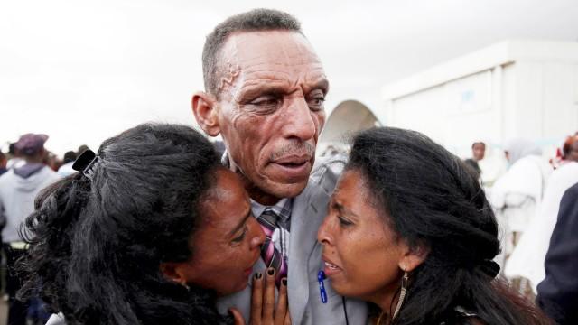 Adisalem Abu reacts as he embraces his twin daughters at Asmara International Airport