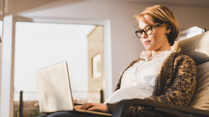 Pregnant woman sitting in armchair using laptop model released Symbolfoto property released PUBLICAT
