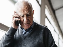 Elderly man reviewing the ceramic vase talking on the phone model released Symbolfoto property rele