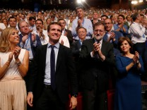 Pablo Casado reacts after being elected as the new leader of Spain's conservative People's Party as his wife Isabel Torres Orts and former Spanish prime minister Mariano Rajoy applaud, in Madrid