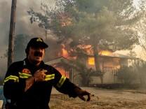 Ein Feuerwehrmann vor einem brennenden Haus bei Athen