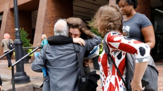 Former New York Daily News newspaper editorial staff members embrace outside the newspaper's offices in New York City after layoffs in New York