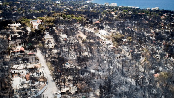 An aerial view shows burnt houses and trees following a wildfire in the village of Mati