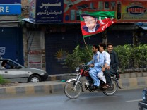 Supporters of Imran Khan, chairman of the Pakistan Tehreek-e-Insaf (PTI), political party wave a party flag as they celebrate during the general election in Rawalpindi