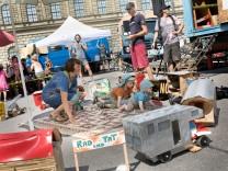 die drei Münchner Wagenburgen demonstrieren auf dem Max-Josef-Platz, weil sie sich durch viele Regeln, Bürokratie usw. aus der Stadt gedrängt fühlen.