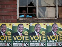 Children look trough a window above election posters of Zimbabwe's ZANU PF leader Emmerson Mnangagwa ahead of general elections, in Mbare township outside the capital Harare