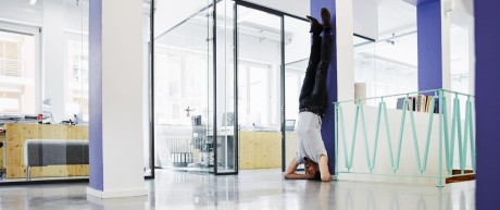 Businessman doing headstand against wall in office model released Symbolfoto property released PUBLI