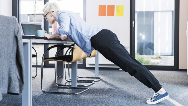 Businesswoman in office doing push ups on desk model released Symbolfoto property released PUBLICATI