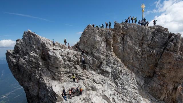 Bergsteiger und Touristen am Gipfelkreuz der Zugspitze
