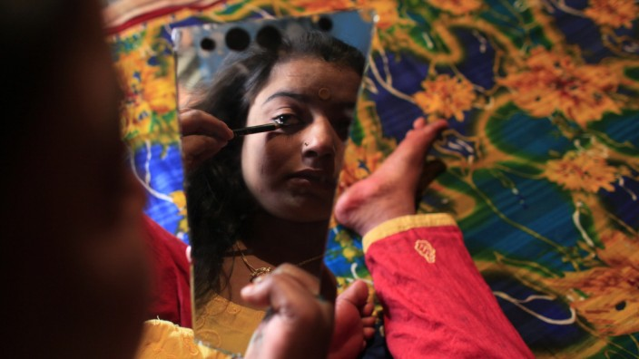 Seventeen-year-old prostitute Hashi applies her makeup as she prepares for customers at Kandapara brothel in Tangail, a northeastern city of Bangladesh
