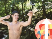 Shirtless young man filming himself with an action video camera in nature model released Symbolfoto
