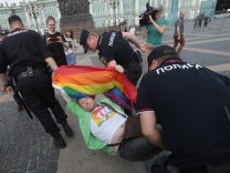 A demonstrator is detained by police during the LGBT community rally in central St. Petersburg