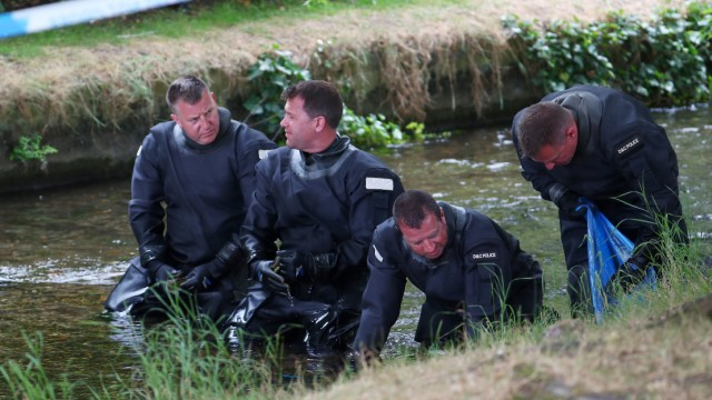 Police officers search a river in Queen Elizabeth Gardens in Salisbury