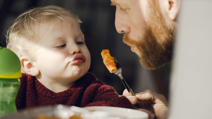 Father feeding his little son with tasty pasta model released Symbolfoto property released PUBLICATI
