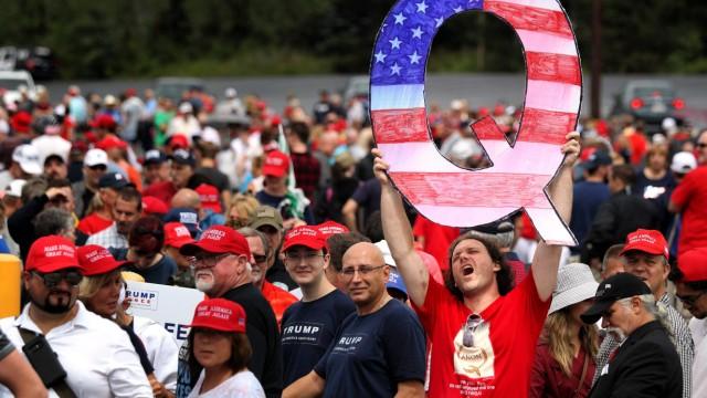 """QAnon: Ein Trump-Anhänger reckt ein großes """"Q"""" in die Luft"""