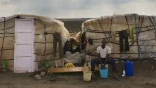 An African immigrant sits by his shack in a makeshift camp in the countryside near the village of Rignano Garganico