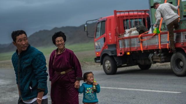 Straßenszene aus der Mongolei: Eine Familie überquert vor einem Transporter die Straße. (Foto: dpa)