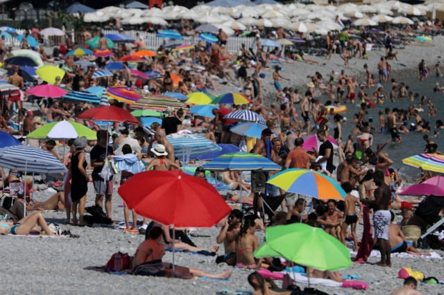Parasols dot a crowded beach of sunbathers in Nice as summer temperatures continue and authorities maintain a heat wave alert in France