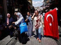 People stroll at Mahmutpasa street, a popular middle-class shopping district, in Istanbul