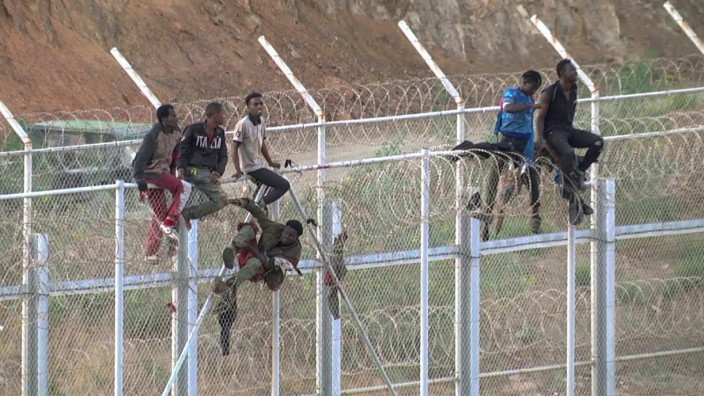 African migrants react in this still image from video as they climb the border from Morocco to Spain's North African enclave of Ceuta