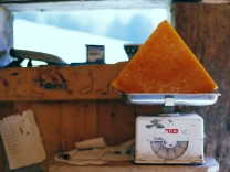 A piece of traditionally made Alp cheese is placed on scales in the cheese storage at the mountain pasture Unterbaergli above Sigriswil