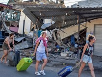 FILE PHOTO - Foreign tourists pull their suitcases as they walk past damaged buildings following a strong earthquake in Pemenang, North Lombok,