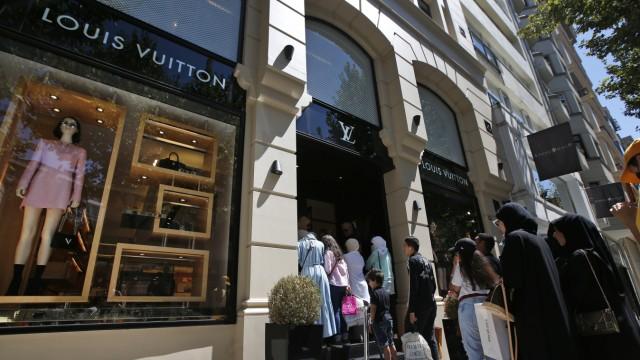 Käufer stehen Schlange vor Luxus-Geschäft.