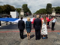 US President Donald Trump and First Lady Melania Trump bid adieu after viewing France's Bastille Day military parade on the Champs-Elysees as the guests of French President Emmanuel Macron and his wife Brigitte Macron, in Paris