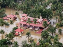 An aerial view shows partially submerged houses and church at a flooded area in the southern state of Kerala
