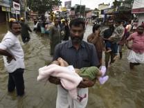 Überschwemmungen in Südindien PATHANAMTHITTA INDIA AUGUST 18 A man carrying a child through the