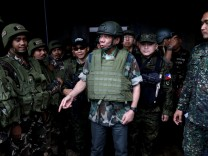 Philippine President Rodrigo Duterte wears a bulletproof vest and a helmet as he gives a pep talk to troops fighting the extremist Maute group in Marawi, Philippines