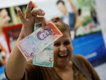 A woman smiles while she shows the new two and five Bolivar Soberano (Sovereign Bolivar) bills, after she withdrew them from an automated teller machine (ATM) at a Mercantil bank branch in Caracas