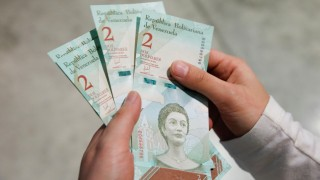 A woman shows the new two Bolivar Soberano (Sovereign Bolivar) bills, after she withdrew them from an automated teller machine (ATM) at the Banesco bank headquarters in Caracas